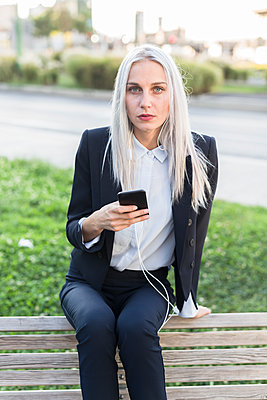 Young businesswoman sitting on bench with cell phone and earphones - p300m1505687 by Giorgio Fochesato