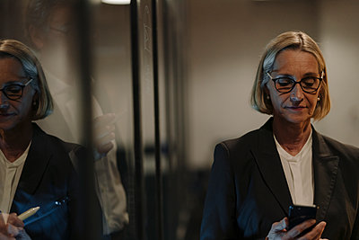 Mature businesswoman using smartphone in officereflected in glass pane - p300m2156092 by Gustafsson