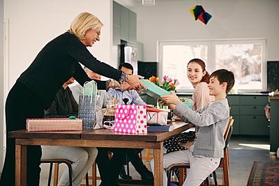 Grandmother giving gift to boy sitting with family at dining table - p426m1580228 by Maskot