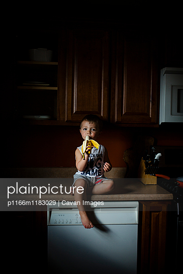 Portrait of boy eating banana while sitting on kitchen counter at home - p1166m1183029 by Cavan Images