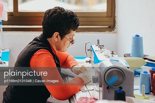 older woman sewing on sewing machine - p1166m2131048 by Cavan Images