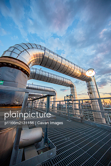 Dusk as viewed through pipe in a refinery - p1166m2131156 by Cavan Images