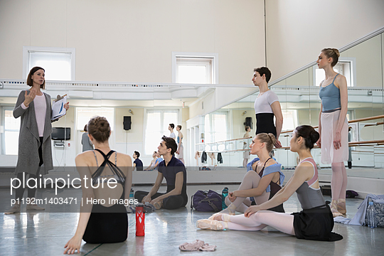 Ballet dancers listening to instructor in dance studio