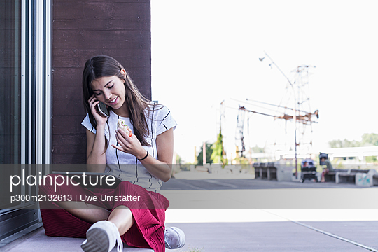 Young woman sitting on windowsill at a building talking on cell phone - p300m2132613 by Uwe Umstätter