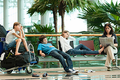 Family waiting in airport terminal - p623m659092f by Thierry Foulon