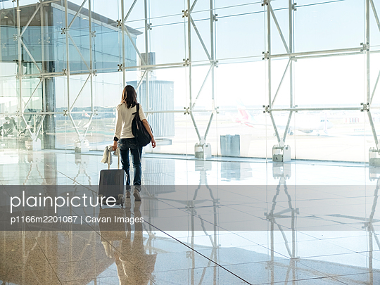 Woman walking with suitcase at the departure hall of the airport. - p1166m2201087 by Cavan Images