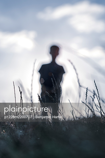 Silhouette of a small boy out walking - p1228m2200707 by Benjamin Harte