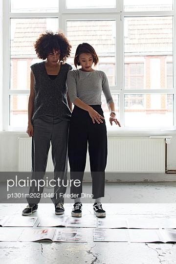 Junge Frauen stehen und schauen auf den Boden - p1301m2021046 von Delia Baum