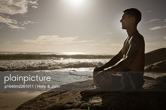 Man practises meditation on the beach at sunset - p1640m2261011 by Holly & John