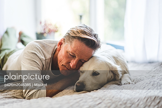 Retired man sleeping with dog comfortably on bed at home - p426m2046385 by Maskot