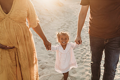 Young family of three walking and playing at beach - p1166m2202114 by Cavan Images
