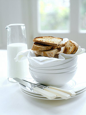 Fresh toast and milk with bowls and knives on table - p349m2167685 by Polly Wreford