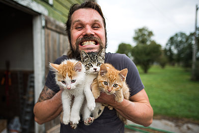 Man grinning with three kittens in arms - p429m2004475 by Viara Mileva