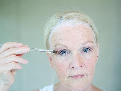 Aeltere Frau traegt Lidschatten auf  - p6430360f von senior images RF