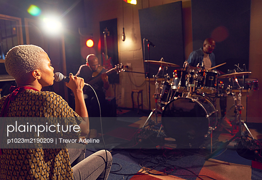 Musicians performing in recording studio - p1023m2190209 by Trevor Adeline