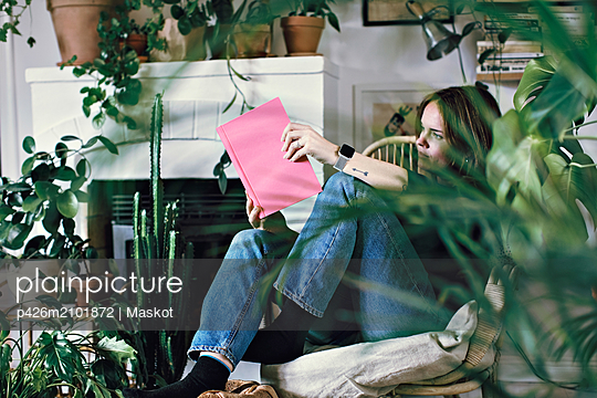 Full length of woman reading book while relaxing on armchair at home - p426m2101872 by Maskot