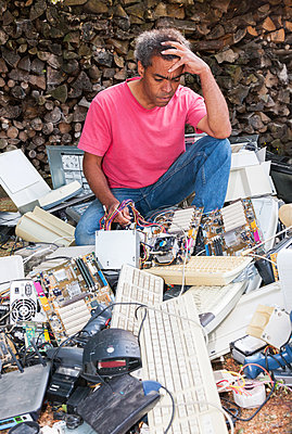 Man sitting in a pile of electronic waste - p1231m1525111 by Iris Loonen