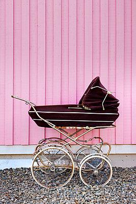 Retro Kinderwagen vor Rosa Wand - p248m816785 von BY