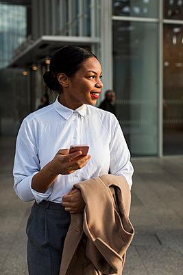Portrait of smiling businesswoman with cell phone - p300m1580845 von Mauro Grigollo