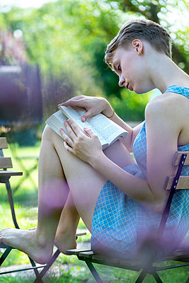 Young woman reading a book in the garden - p427m2134493 by Ralf Mohr