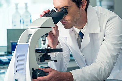 Biologist using microscope - p623m1045591f by Frederic Cirou