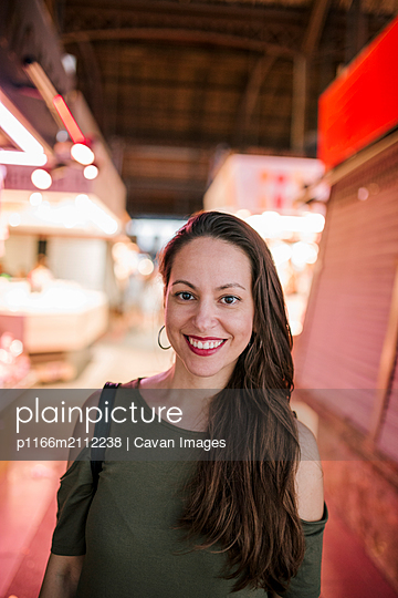 Portrait of smiling woman standing in illuminated shopping mall - p1166m2112238 by Cavan Images