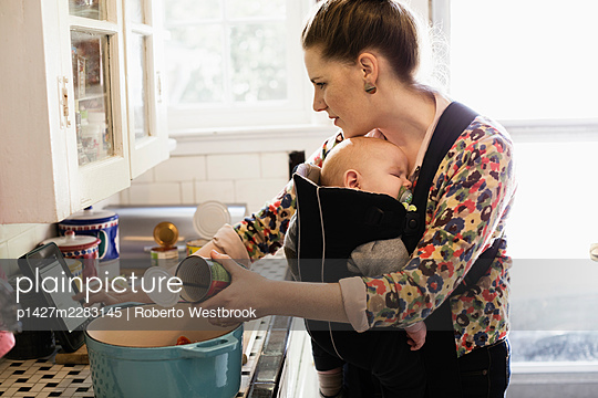 Mid adult mother with baby son in sling preparing food in kitchen - p1427m2283145 by Roberto Westbrook