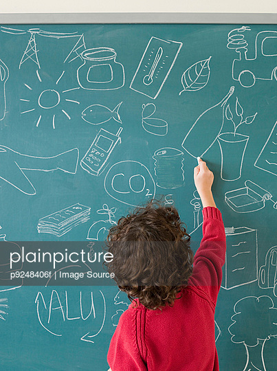 Boy writing on a blackboard - p9248406f by Image Source
