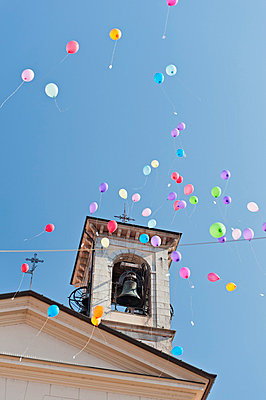 View of balloons flying at bell tower of church - p30020962f by Holger Spiering