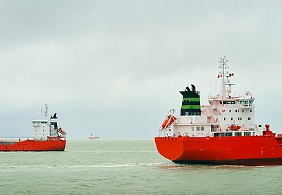 Ships with red hull pass each other on the North Sea - p429m1118348f by Mischa Keijser