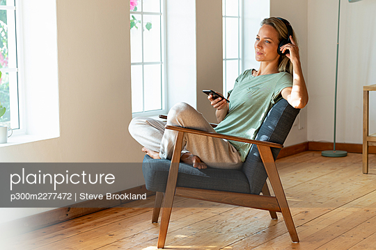 Contemplating woman listening music and holding smart phone on chair at home - p300m2277472 by Steve Brookland