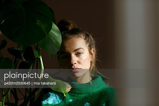 Junge Frau hält Topfpflanze in der Hand - p432m2030645 von mia takahara