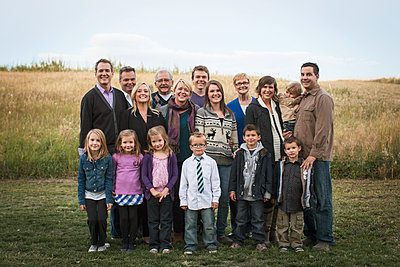 Family portrait of seventeen people standing outdoors. - p1192m1132236f by Hero Images