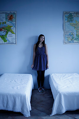 Young woman standing between two beds - p1521m2128964 by Charlotte Zobel