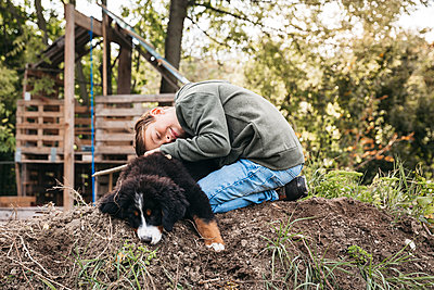 Boy playing with his Bernese mountain dog in the garden - p300m2143800 von Epiximages