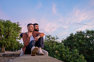 Affectionate gay couple sitting on a wall at sunset - p300m2154485 von VITTA GALLERY