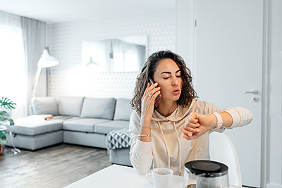Portrait of woman looking at her smartwatch at home - p300m2160679 von Katharina Mikhrin