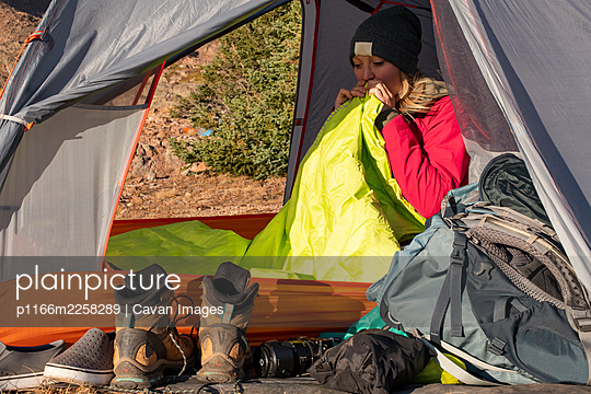 Young woman blowing mattress while camping on mountain during vacation - p1166m2258289 by Cavan Images