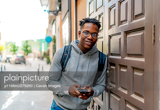 young african man using his smartphone in the city - p1166m2279260 by Cavan Images