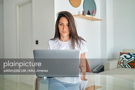 Mid adult woman using laptop at home - p300m2282128 by Kiko Jimenez