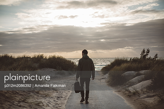 Man walking on beach - p312m2086392 by Amanda Falkman