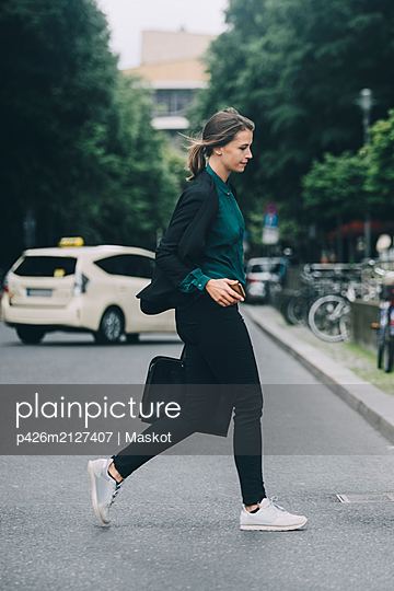 Side view of creative businesswoman crossing street in city - p426m2127407 by Maskot