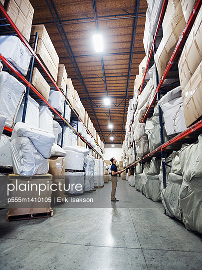 Caucasian worker checking inventory in warehouse - p555m1410105 by Erik Isakson