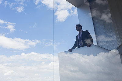 Businessman on modern balcony looking out window at blue sky and clouds - p1023m1519876 by Martin Barraud