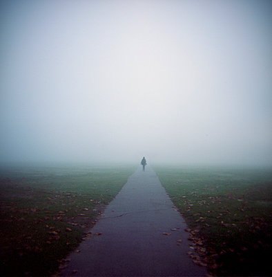 Distant silhouetted female figure on path in foggy park - p1072m829416 by Neville Mountford-Hoare