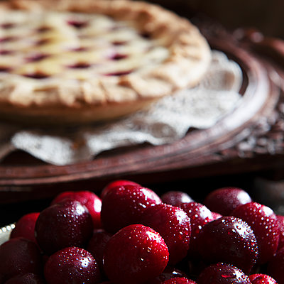 fresh cherries ,cooked pie in the background blured for text overlay - p1166m2201714 by Cavan Images