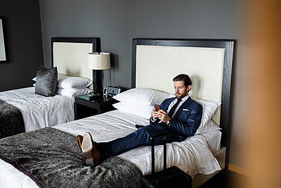 Businessman using smart phone on bed in hotel room - p1192m2047136 by Hero Images
