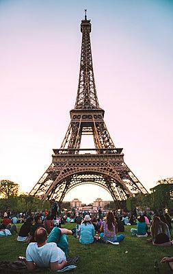 France, Paris, Champ de Mars, people looking at Eiffel Tower by sunset - p300m1196914 by Gemma Ferrando