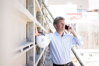 Man on cell phone on construction site - p300m2004242 by Robijn Page