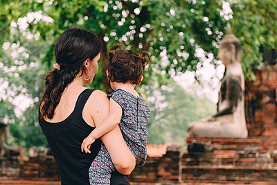Thailand, Ayutthaya, Mother and daughter looking at a Buddha statue at Wat Mahathat - p300m2058722 von Gemma Ferrando